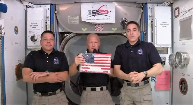Space station crew with flag
